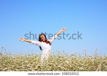 Happy woman in beauty field with white flowers