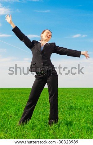 happy woman in black costume standing at the green field