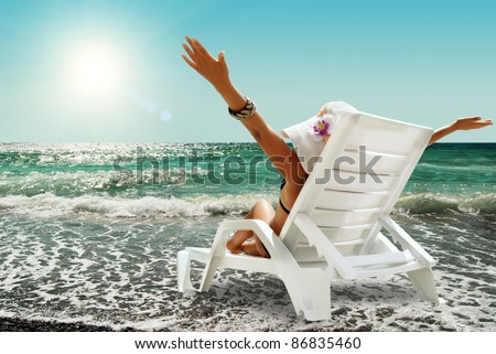 Happy woman in chaise lounge on the sea beach in sunny day - stock photo