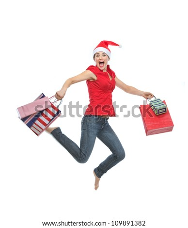 Happy woman in Christmas hat with shopping bags jumping - stock photo