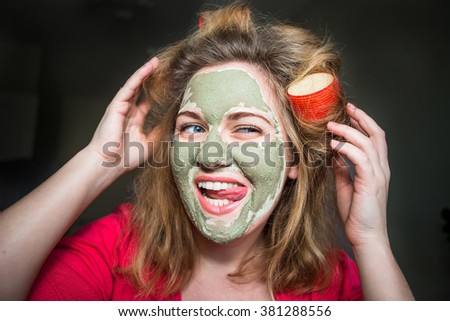 Happy woman in curlers and a mask on his face, fooling around joking