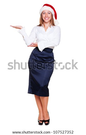 happy woman in formal wear and santa hat holding empty copyspace on her open palm over white background