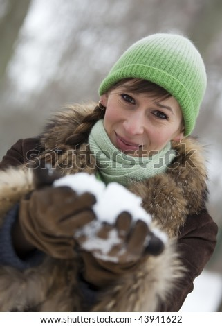 happy woman in fur coat holding snow in her hands