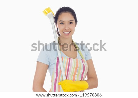 Happy woman in gloves with broom on her shoulder - stock photo