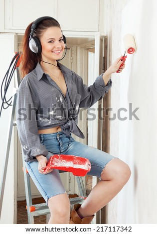 Happy  woman in headphones  makes repairs in the apartment - stock photo