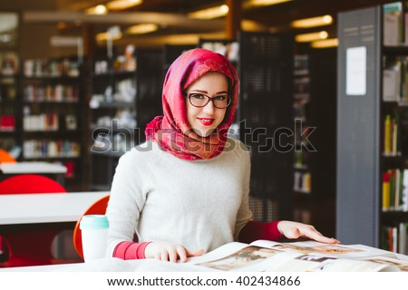 Happy woman in headscarf read a book at the library - stock photo