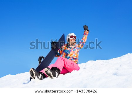 Happy woman in pink sit in snow holding snowboard waiving hands, with mountains on blue sky background