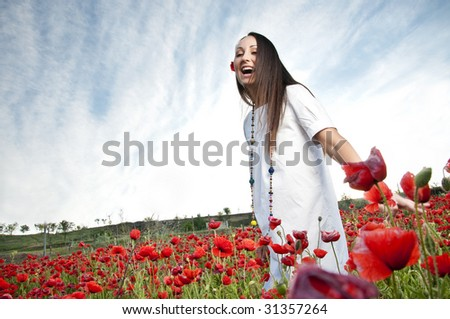 Happy woman in poppy field - stock photo