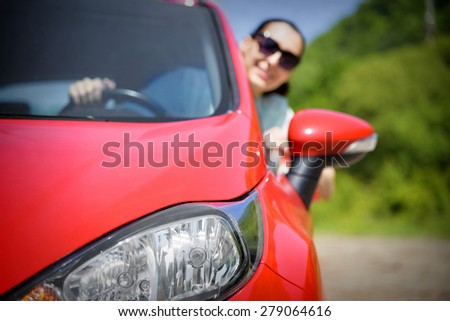 Happy woman in red car. Focus on headlight.