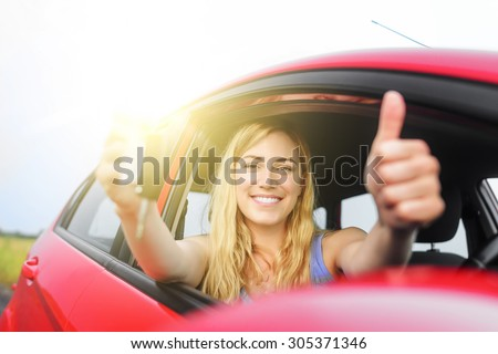 Happy woman in red car showing thumb up and key. - stock photo
