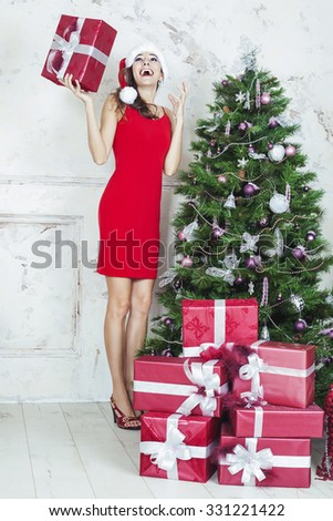 Happy woman in santa claus hat holding present next Christmas tree and gifts