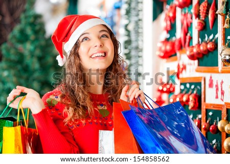 Happy woman in Santa hat looking up while carrying shopping bags at store - stock photo