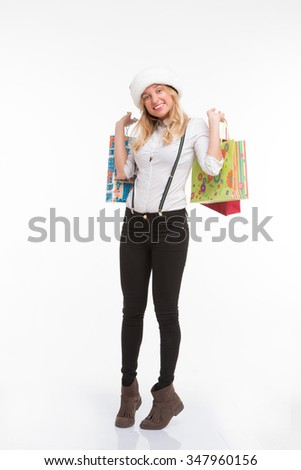 Happy woman in Santa hat smiling and holding packeges with presents for her relatives, friends in New Year or Christmas holidays.