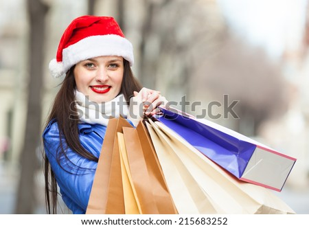 Happy woman in Santa hat with purchases at street during the Christmas sales