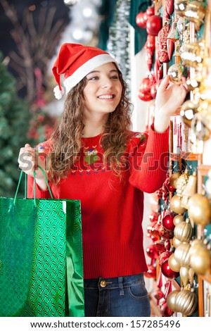 Happy woman in Santa hat with shopping bag buying Christmas ornaments at store - stock photo