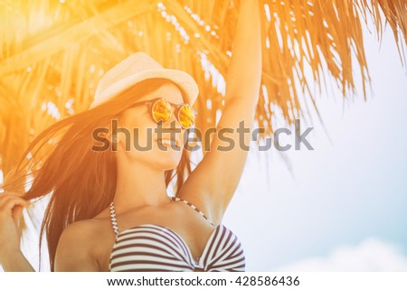 Happy woman in summer sun on the beach during tropical vacation - stock photo