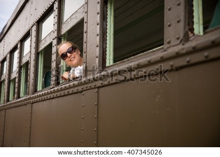 Happy woman in sun glasses sitting in the old train and looking out the window. view from outside. Girl in retro train. Vacation trip. - stock photo