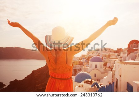 Happy woman in sun hat enjoying her holidays on Santorini, Greece. View on Caldera and Aegean sea from Oia. Active, travel, tourist concepts - stock photo