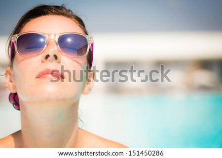 Happy woman in sunglasses looking at the sun - stock photo