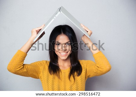 Happy woman in sweater holding laptop above her head like a roof over gray background. Looking at camera - stock photo