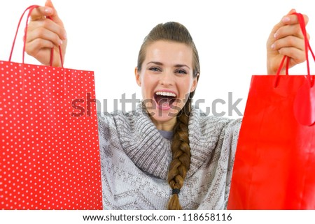 Happy woman in sweater showing red shopping bags - stock photo