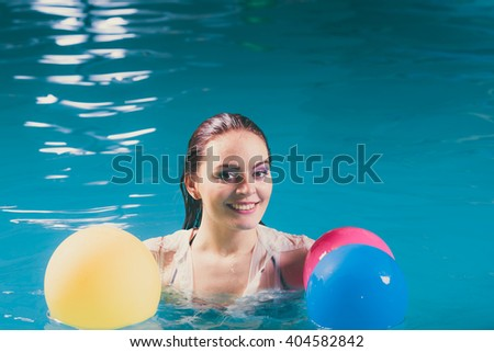 Happy woman in swimming pool water having fun with balloons. Seductive young girl wearing wet white shirt relaxing. - stock photo