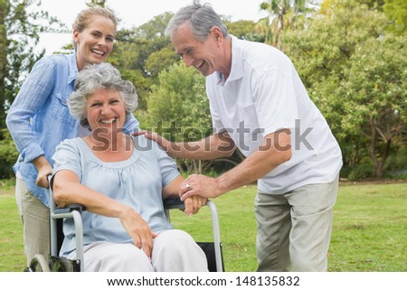 Happy woman in wheelchair with daughter and husband in the park laughing on sunny day - stock photo