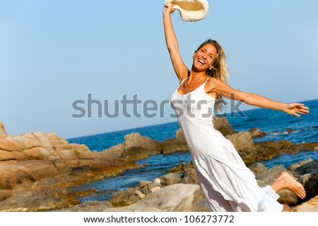 Happy woman in white dress jumping on beach. - stock photo