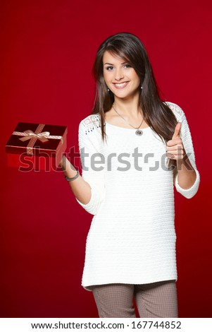 Happy woman in white sweater with gift box showing thumb up - stock photo