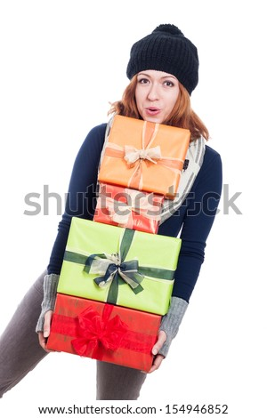 Happy woman in winter clothes carrying many presents, isolated on white background. - stock photo