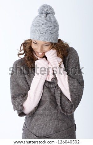 Happy woman in winter outfit smiling over white background, wearing hat and warm sweater.