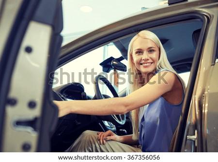 happy woman inside car in auto show or salon - stock photo