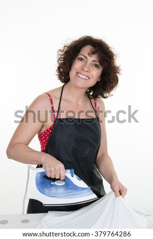 Happy Woman Ironing Trousers With Electric Iron At Home - stock photo
