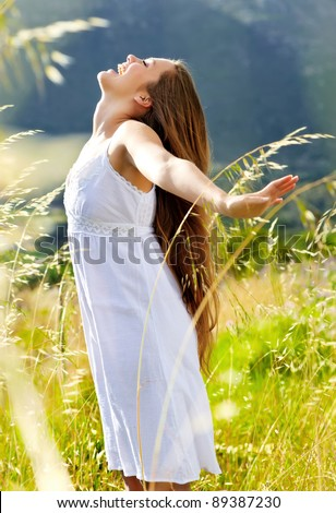 happy woman is at peace in the sunlight, carefree summer concept - stock photo