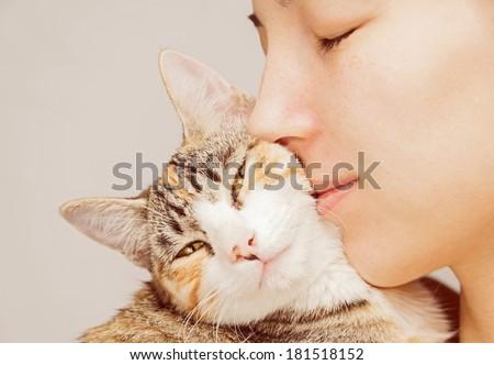Happy woman is hugging orange tabby feline - stock photo