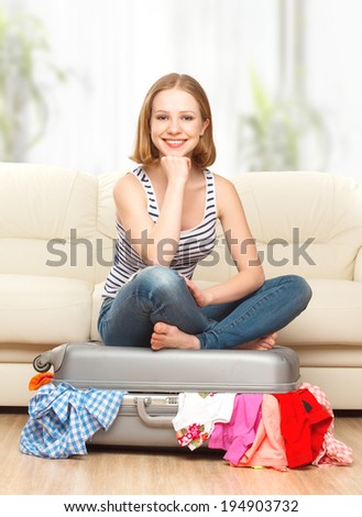 happy woman is packing a suitcase at home - stock photo