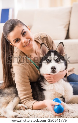 Happy woman is playing with her dog at home.