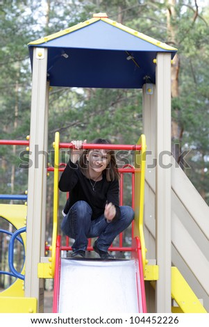 Happy woman is posing on a slide in summer - stock photo
