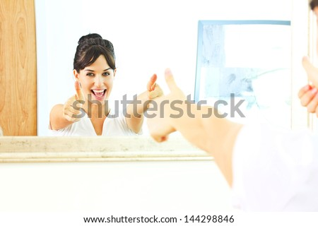 happy woman is showing her thumb in mirror's reflection - stock photo