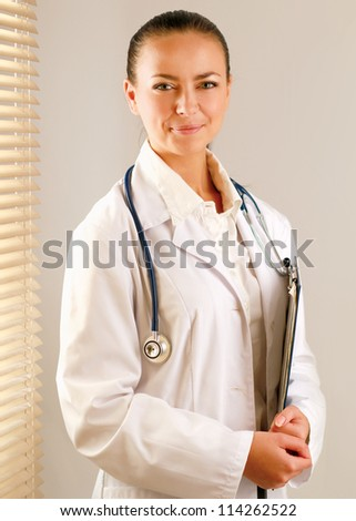Happy woman is standing near window and examining x-ray - stock photo