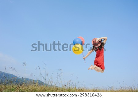 Happy Woman Jumping and holding balloon with blue sky outdoor.Summer Vacation concept - stock photo