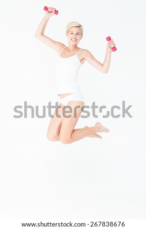Happy woman jumping and holding dumbbells on white background - stock photo