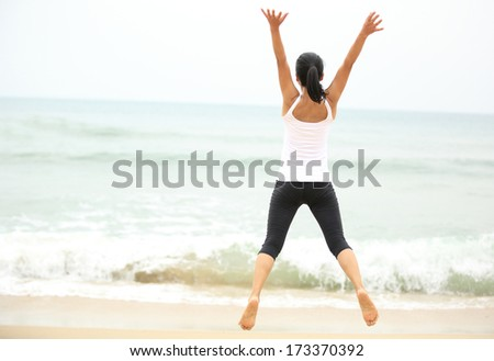 happy woman jumping at seaside beach in summer holidays  - stock photo
