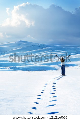 Happy woman jumping at winter mountains, active female enjoying nature, girl playing in the snow, teen having fun outdoor, healthy lifestyle and wintertime holidays vacation concept - stock photo