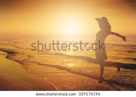 Happy Woman Jumping in Sea  beach Sunset silhouette. - stock photo