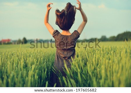 Happy woman jumping in the green field - stock photo