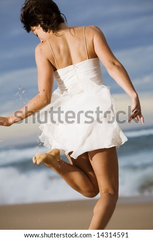 Happy woman jumping on beach in white dress