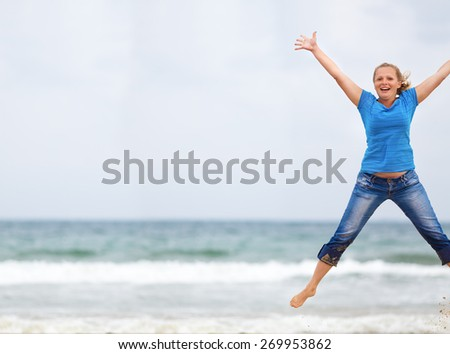 Happy woman jumping on the beach against the sea and cloudless sky. Selective focus. Space for text. Shallow depth of field. Focus on model. - stock photo