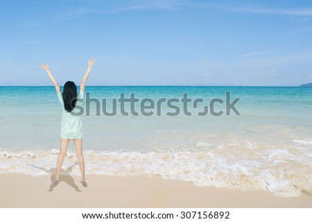 Happy Woman jumping on the beach and clouds  sky.Summer holiday concept. - stock photo