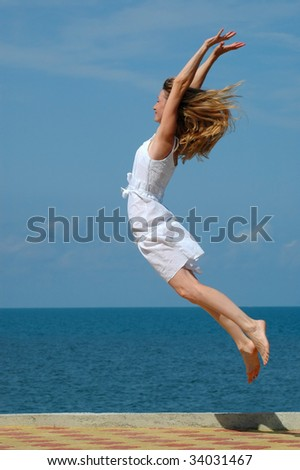 Happy woman jumps in blue sky